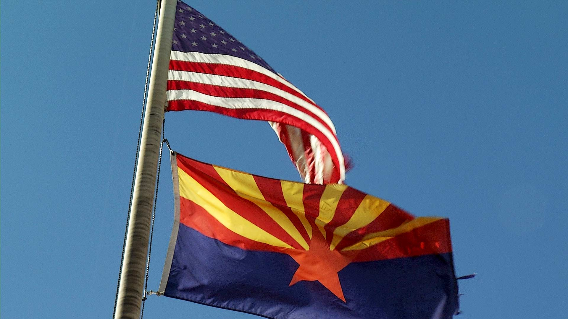 A flag post carrying both the Arizona flag and United States flag wave in the wind.