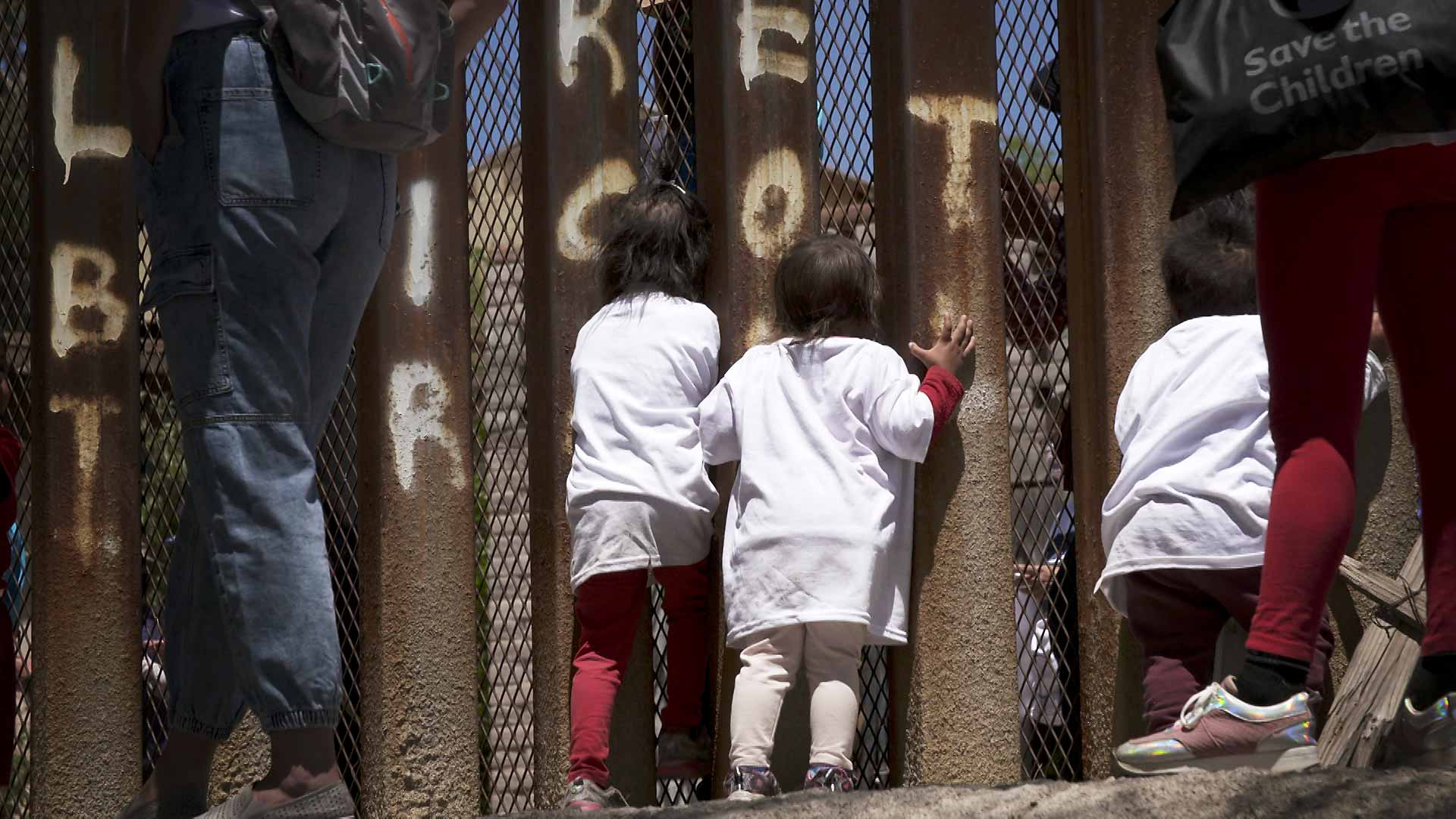 Children peer through the border fence in Nogales, Sonora during a march led by migrants on April 30, 2021 who wanted to call attention to immigration policies in the United States that have prevented them from entering the country while they seek political asylum.