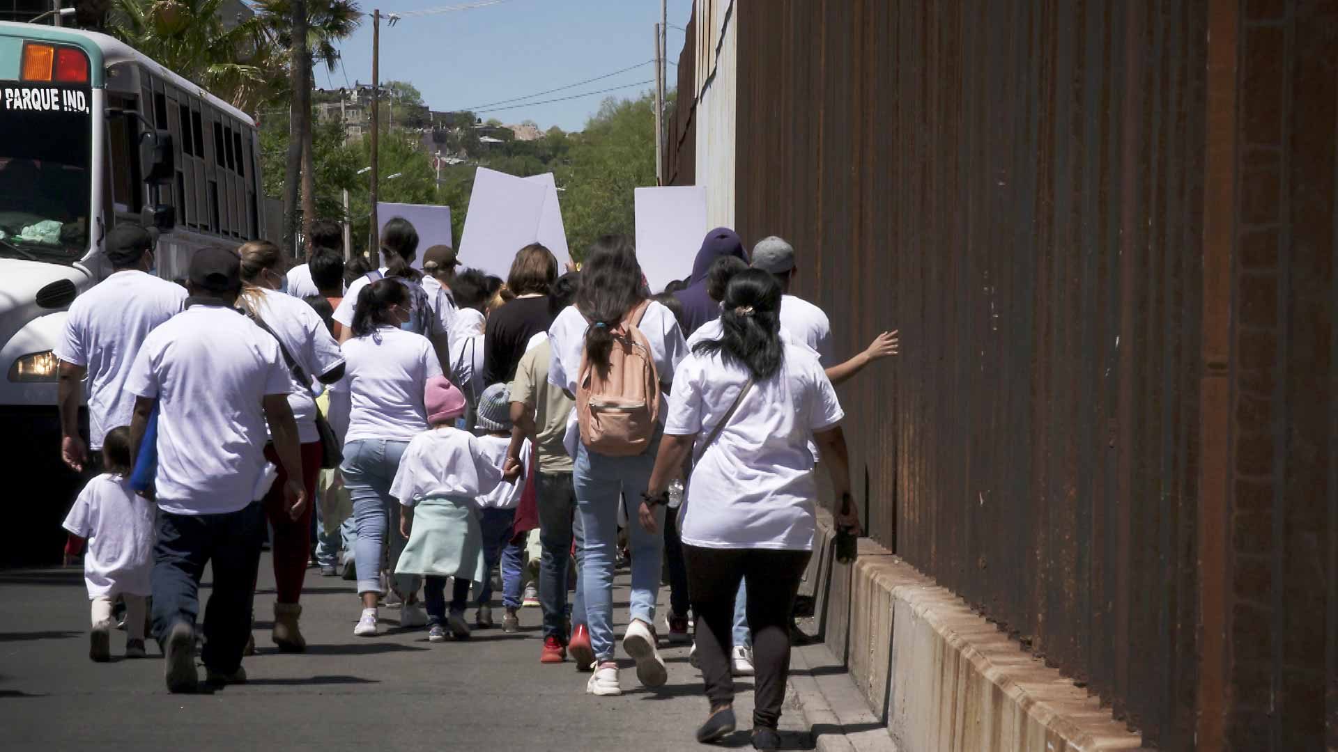 A group of demonstrators walk along the border wall in a march led by migrants and asylum seekers in Nogales, Sonora on April 30, 2021. The event was meant to urge President Biden to act on immigration reform.
