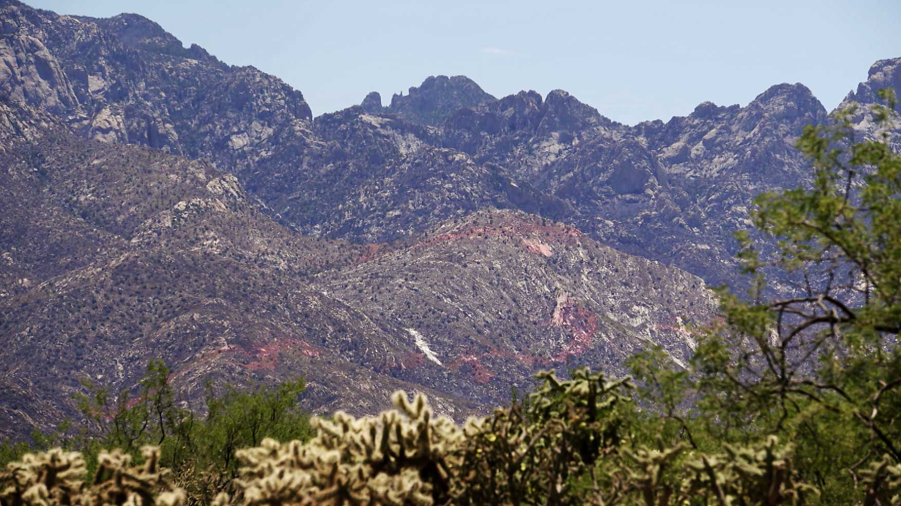 Red fire retardant is visible on parts of the Santa Catalina Mountains as a result of firefighting efforts against the Bighorn Fire. June 2020.