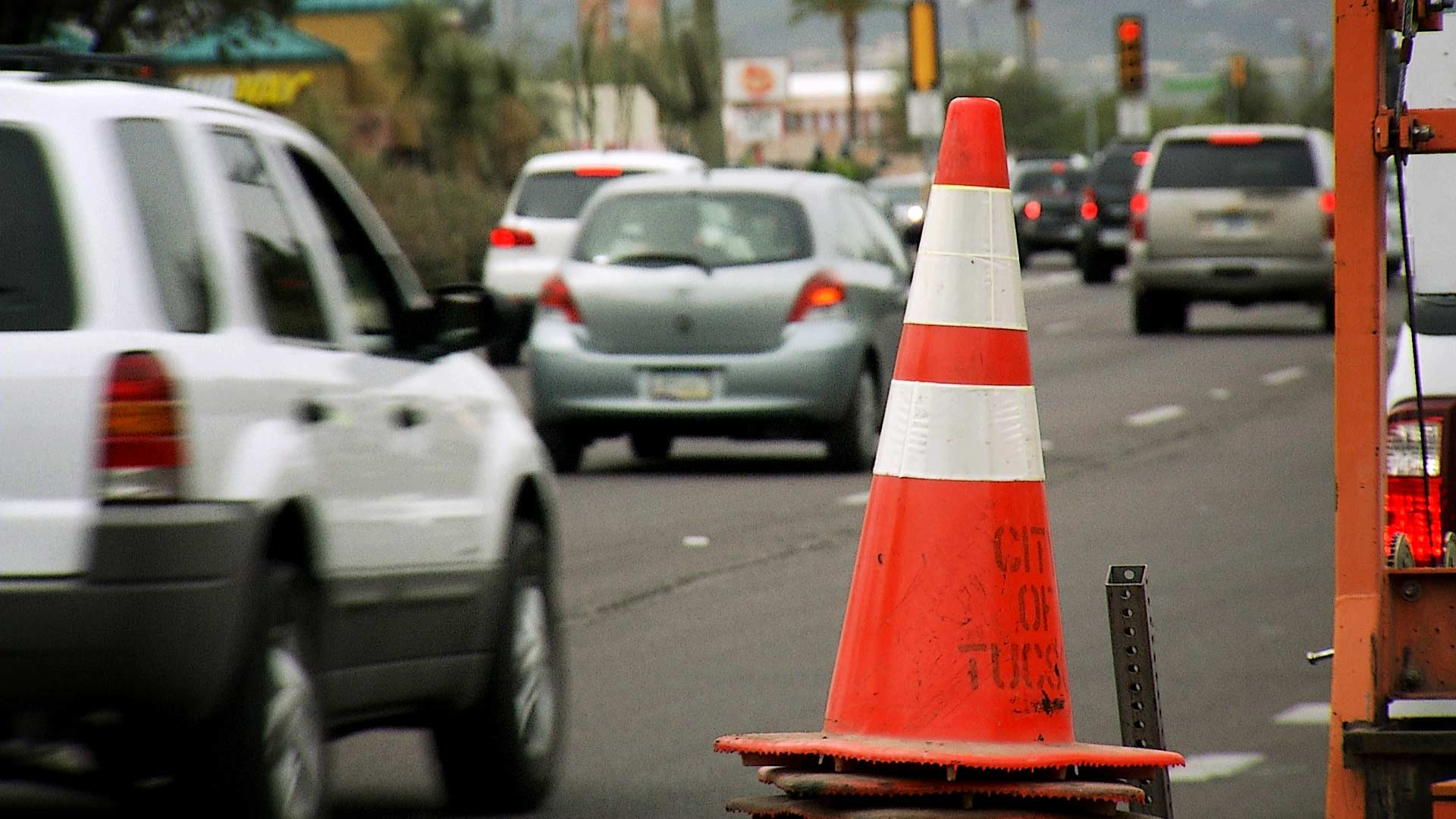 A traffic cone along Speedway Boulevard as traffic passes in the background.