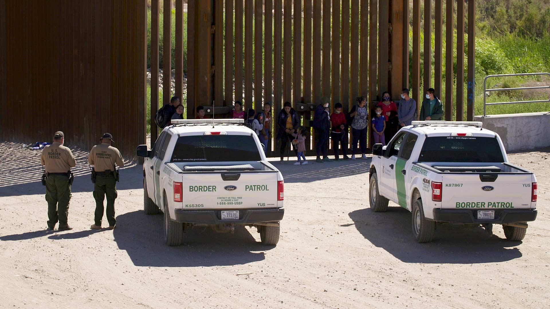 A group of migrants and Border Patrol agents along the border fence in Yuma County. June 2021.