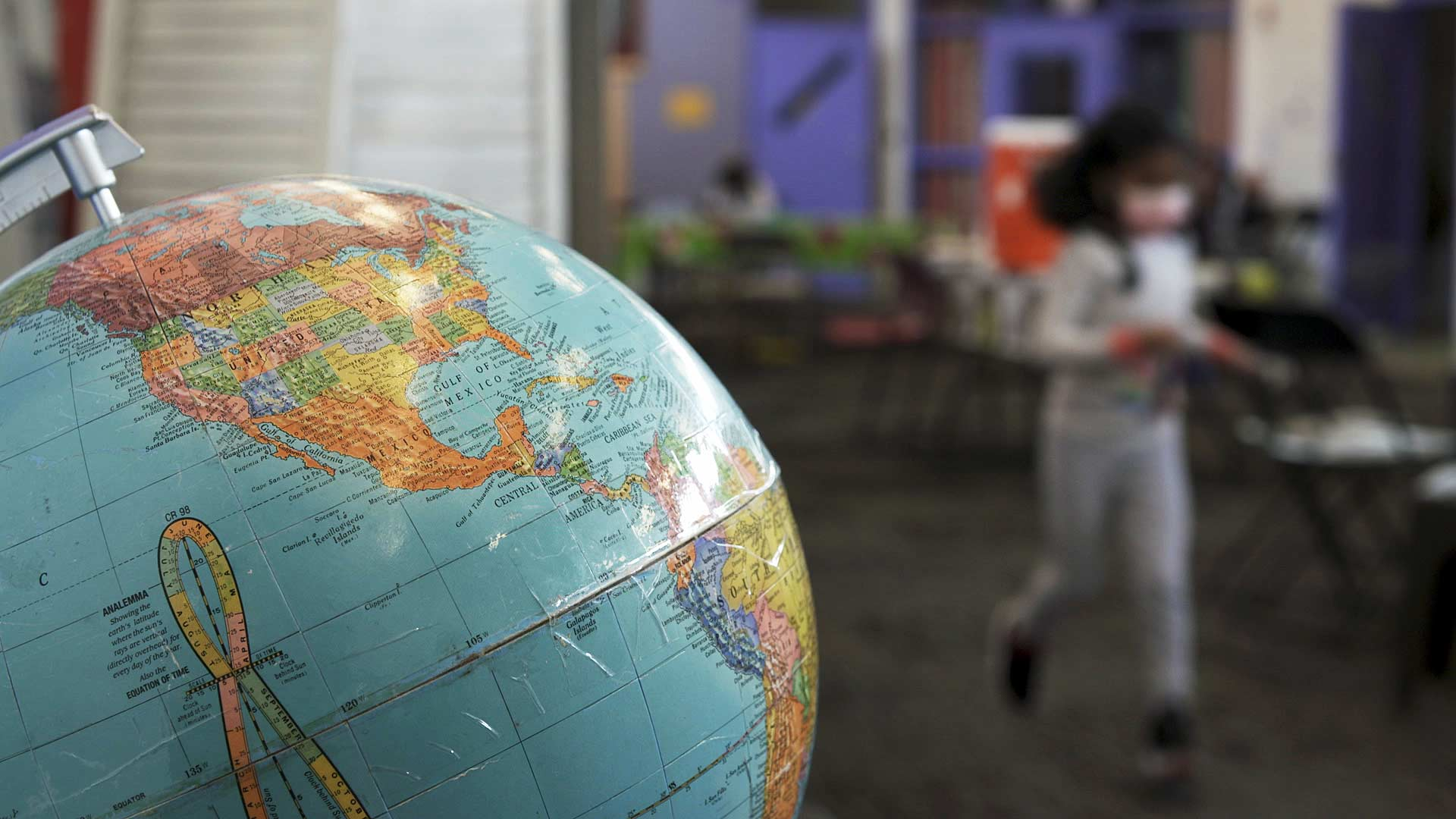 A globe is visible in the foreground as a child runs past at Casa Alitas in Tucson. The nonprofit offers shelter, medical aid and helps arrange travel for migrants admitted into the United States.