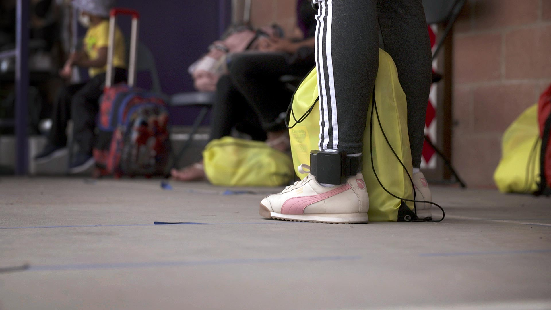 A GPS ankle bracelet is visible on the ankle of a migrant at Casa Alitas in Tucson. June 2021.