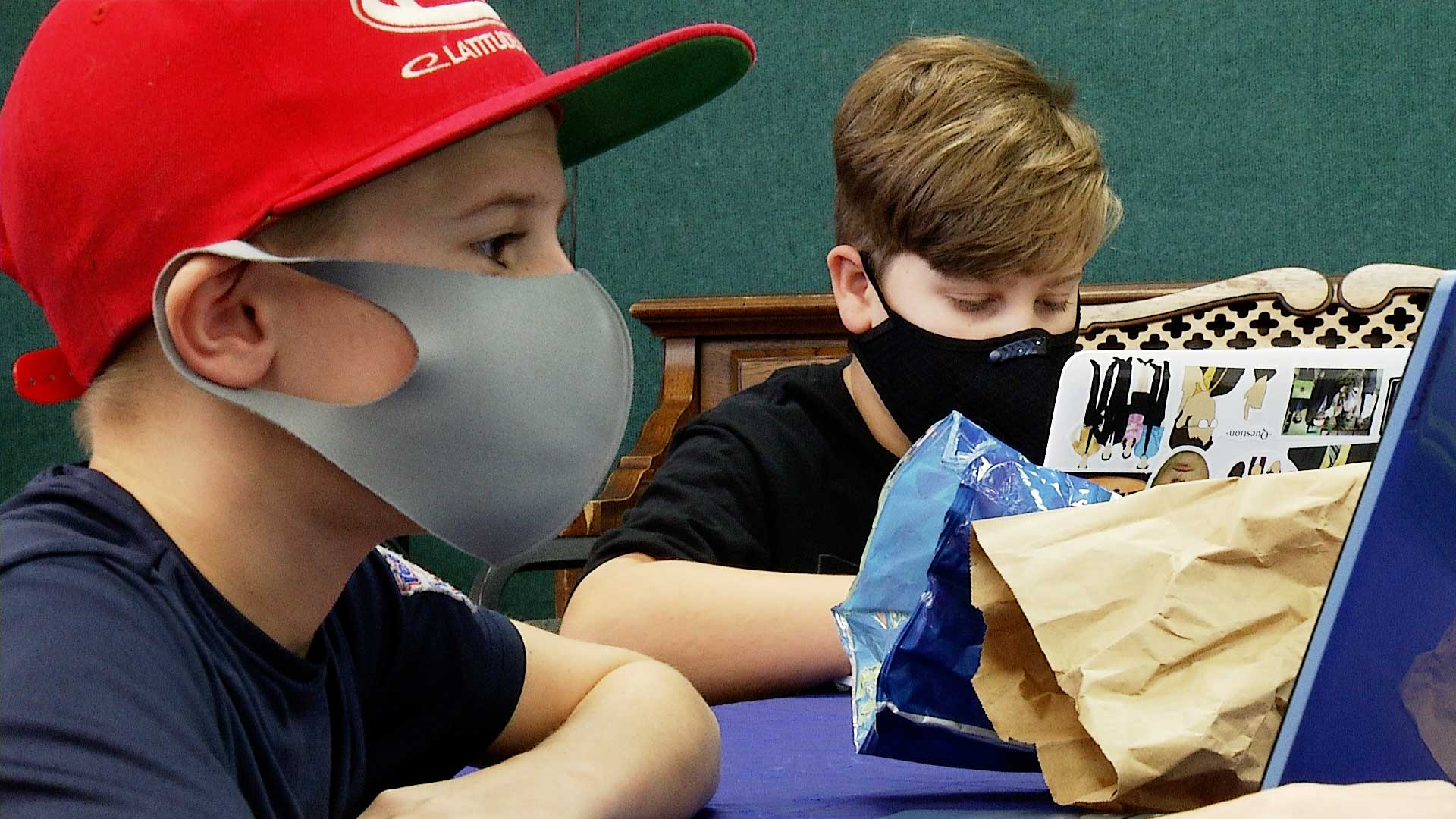 Two mask-wearing boys work on their laptops at the Jewish Community Center in Tucson. September 2021.