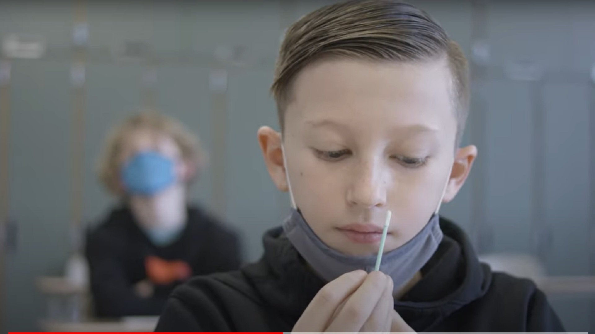 """An elementary school student prepares to self-administer a COVID-19 test in a frame from a promotional video by Ginkgo Bioworks, which distributes """"pooled testing"""" systems to schools around the country."""