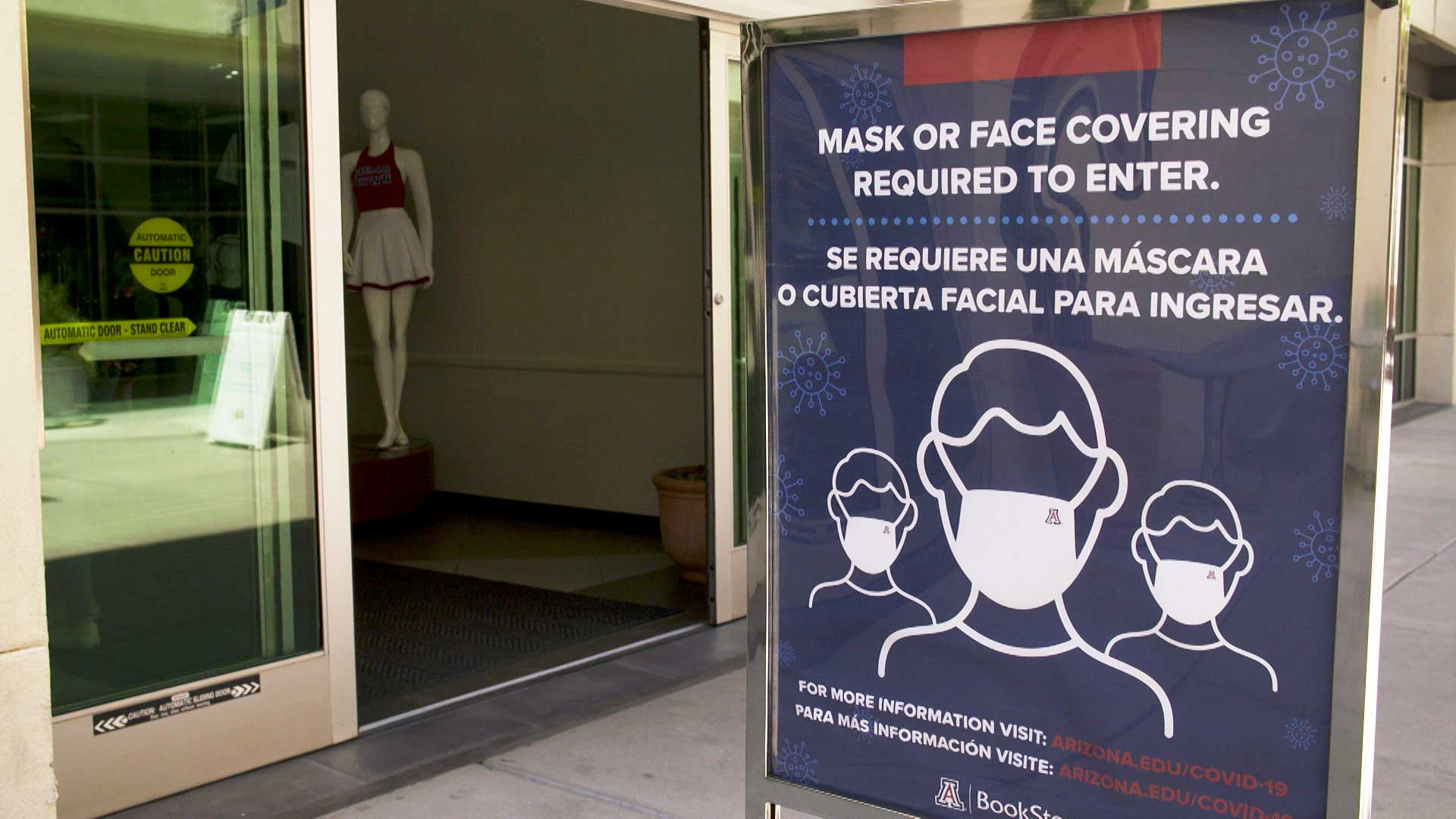 A sign posted outside the University of Arizona BookStores at the Student Union reminds customers that masks are required to shop inside.