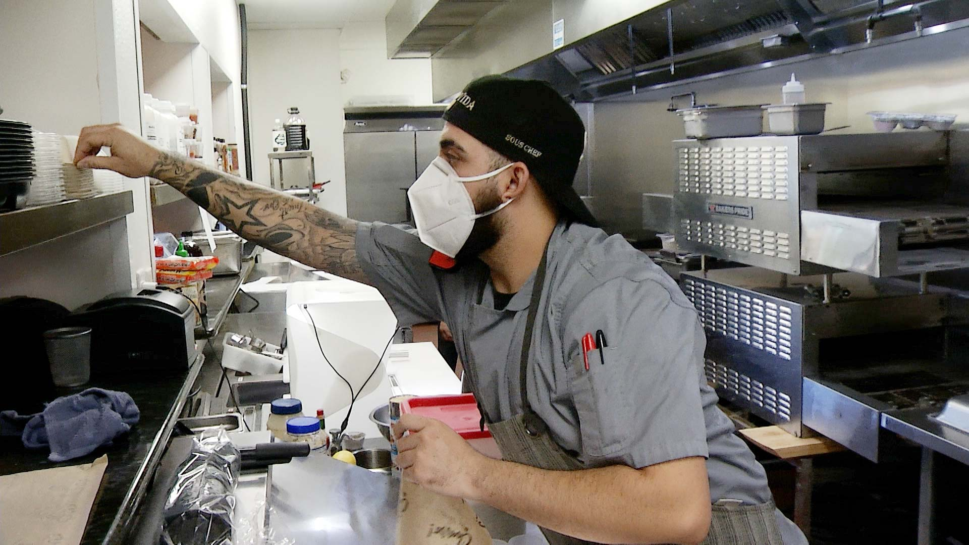 A sous chef prepares orders while masked inside the kitchen at Barrio Charro in Tucson.