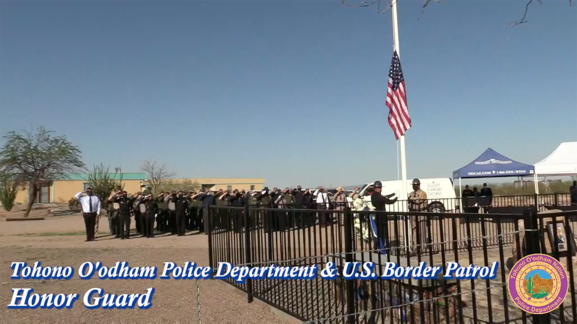 Uniformed personnel saluting during Tohono O'odham Nation Officer Bryan Brown's memorial service August 27, 2021, a year after his death.