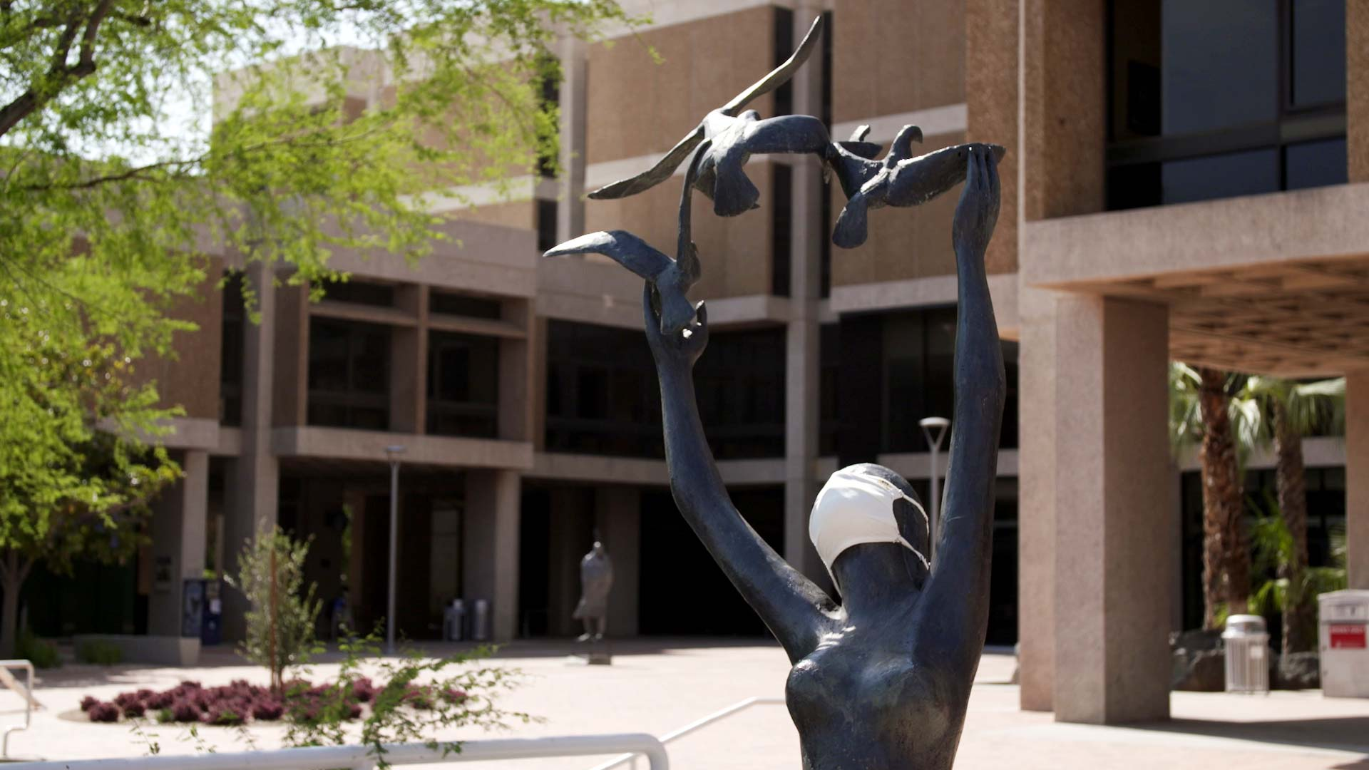 A sculpture outside of the University of Arizona's Main Library is donned with a face mask.