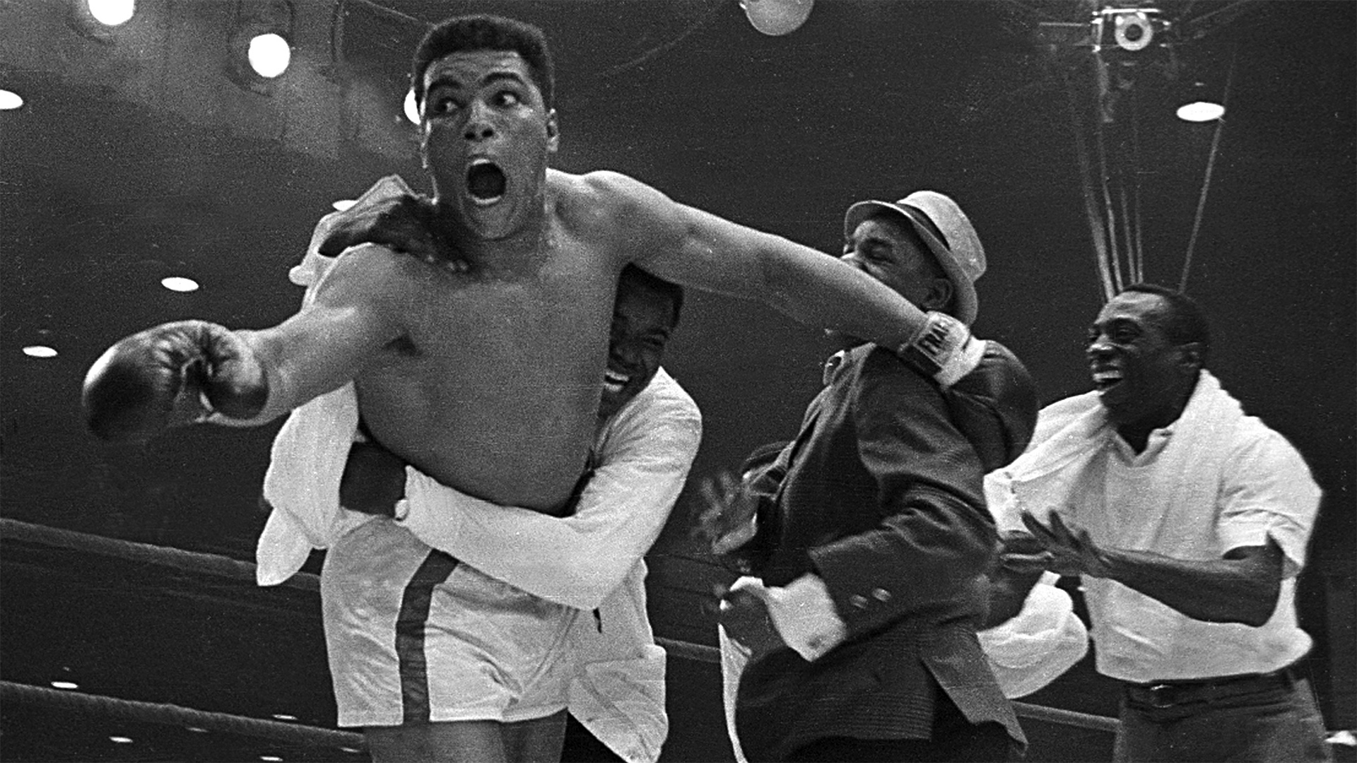Cassius Clay's handlers hold him back after he is announced the new heavyweight champion of the world after knocking out Sonny Liston. Bundini Brown embraces Ali. Luis Sarria runs to the group in a smile on the right. Miami, Florida. February 25, 1965.