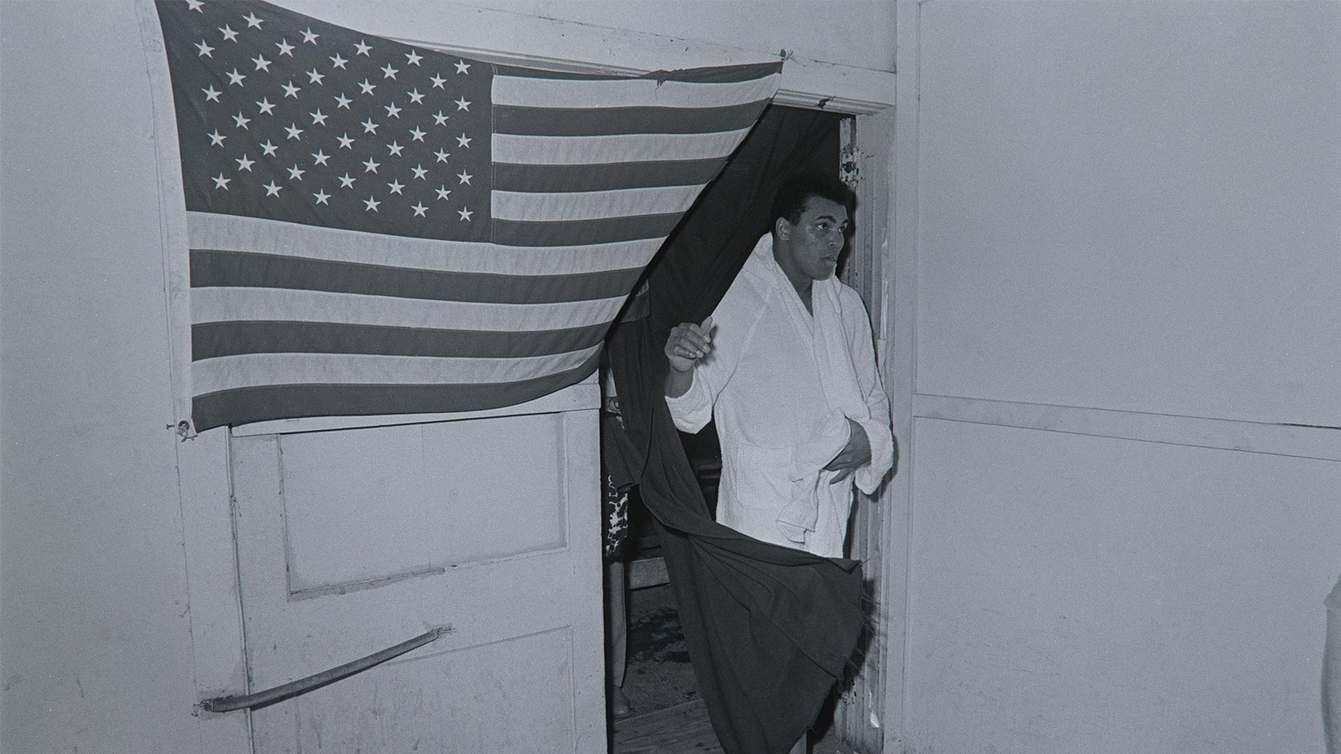 Muhammad Ali coming through doorway draped in a United States flag. Fifth Street Gym. Miami, FL. February 25, 1971.