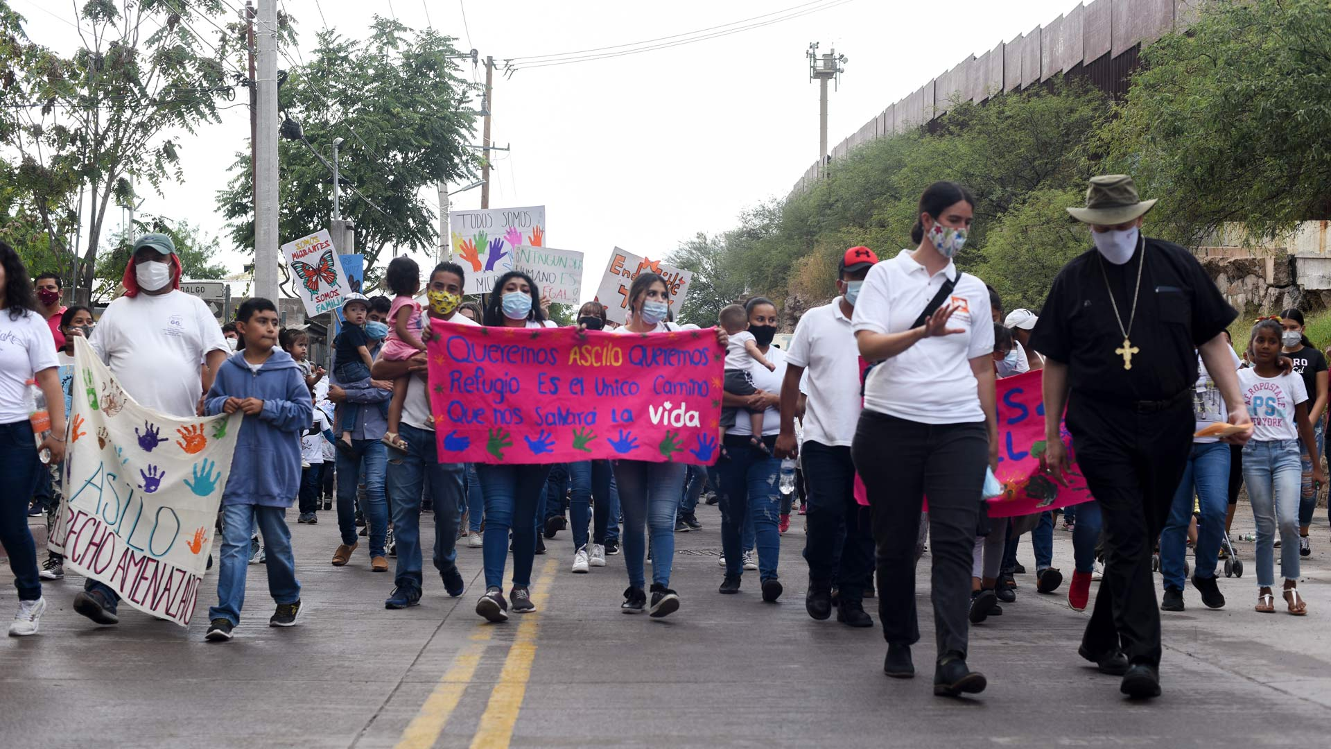 Migrants march toward the Deconcini Port of Entry in Nogales, Sonora in a demonstration asking President Joe Biden to restore the U.S. asylum process.
