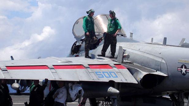 Airmen inspect a Prowler on board the USS Nimitz.