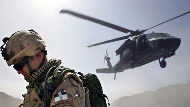soldier turns his back away from a dust cloud kicked up by a Blackhawk helicopte