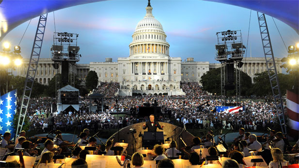 Conductor Jack Everly leads the National Symphony Orchestra before a crowd of thousands on the West Lawn of the U.S. Capitol.